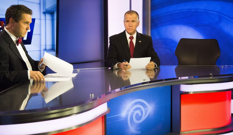 State Speaker of the House, Thom Tillis, prepares to answer questions during a live televised roundtable hosted by Tim Boyum, left, Tuesday, Oct. 21, 2014, at Time Warner Cable News studios in Raleigh, N.C. Time Warner Cable News initially billed the program as a debate between Tillis and other candidates. But Democratic incumbent Kay Hagan declined a few months ago to participate. An empty seat was placed next to Tillis. Libertarian Sean Haugh didn't meet debate qualifications. (AP  Photo/The News & Observer, Travis Long, Pool)