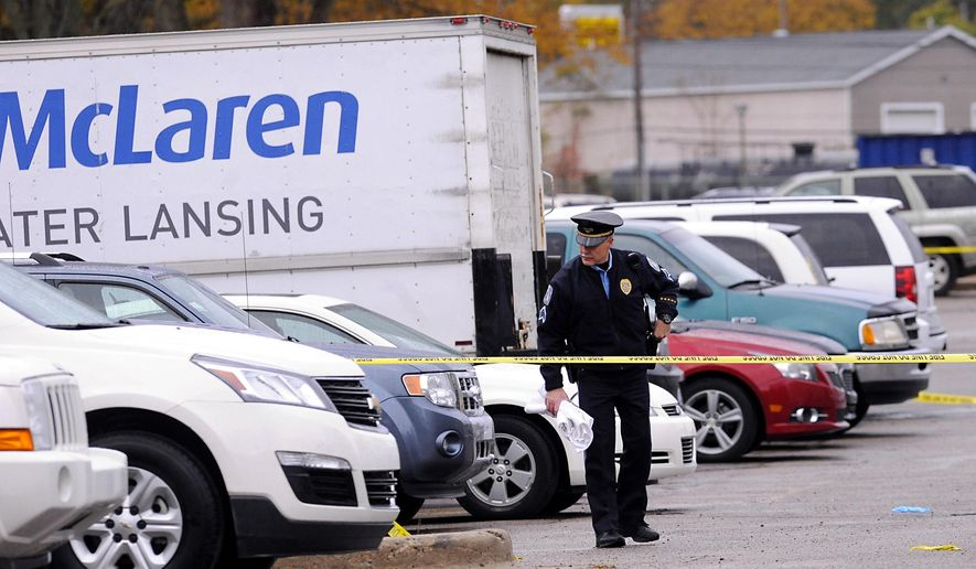 Lansing Police investigate the scene of a double fatal shooting in the parking lot behind the McLaren Greater Lansing Pennsylvania campus in Lansing, Mich., Tuesday, Oct. 21, 2014. Lansing police say two people are dead after a murder-suicide in a hospital parking lot. (AP Photo/Lansing State Journal, Rod Sanford) NO SALES