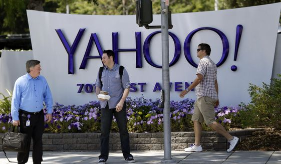 In this June 5, 2014 photo, people walk in front of a Yahoo sign at the company's headquarters in Sunnyvale, Calif. Yahoo Inc. reports quarterly financial results on Tuesday, Oct. 21, 2014. (AP Photo/Marcio Jose Sanchez)