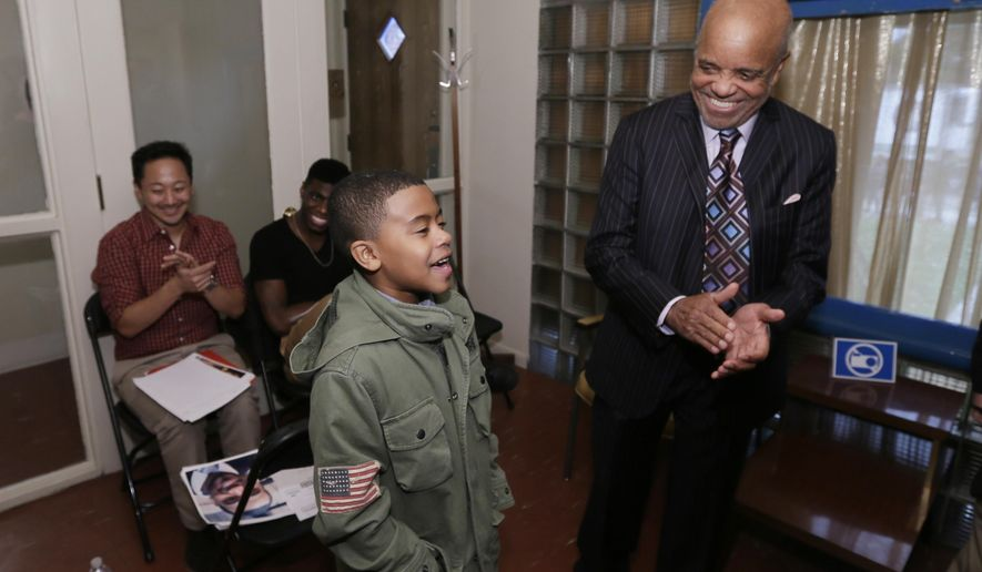 "Motown Records founder Berry Gordy, right, listens as Chase Harris, 9, sings at the Motown Museum in Detroit, Tuesday, Oct. 21, 2014. The makers of ""Motown the Musical"" held an open casting call for the ongoing Broadway show and national tour. The hit show about Gordy tells the story of how his Motown Records empire rose and fell and then rose again. (AP Photo/Carlos Osorio)"