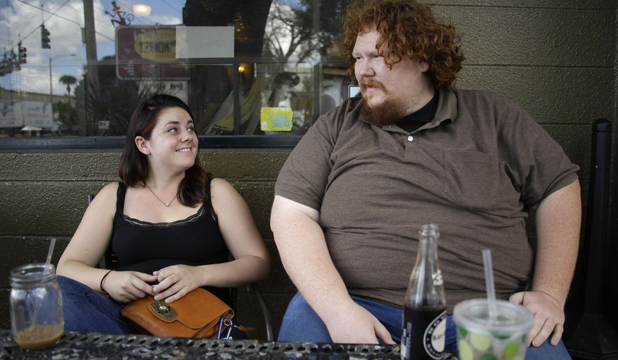 In this Monday, Oct. 13, 2014 photo, Tim Murphy, right, talks with friend Alsion Sherberg at a cafe in Orlando, Fla. Murphy is one of a growing number of young voters in Florida choosing no party affiliation over Republican or Democrat.  (AP Photo/John Raoux)