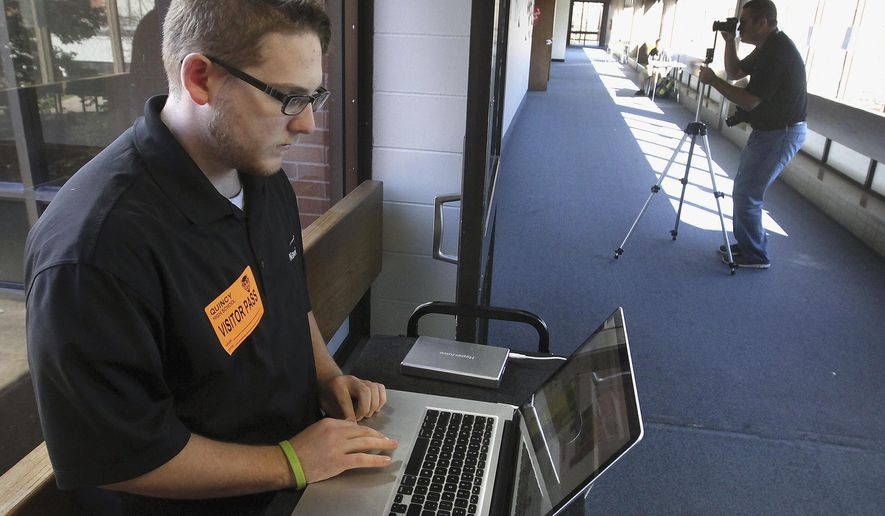 "In this Oct. 16, 2014 photo, Trevor Petitte, information technology specialist, left, and Thom Jones, director of sales at Ohio-based Lauren Innovations, gather photographic information at Quincy Senior High School in Quincy, Ill.  The Quincy School District is one of five districts in Illinois testing an emergency response system, involving the use of the ""NaviGate Prepared"" security system, that gives first responders instant access to information such as building layouts before, during and after a crisis. The system stores school information on the Internet so first responders can access it immediately. (AP Photo/The Quincy Herald-Whig, Steve Bohnstedt)"