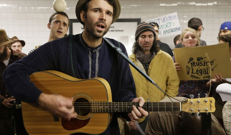 Andrew Kalleen joins other performers during a protest in the Metropolitan Avenue Subway station Tuesday, Oct. 21, 2014, in New York. Kalleen, 30, was performing Friday, Oct. 17 at the G-train stop in Brooklyn's hipster Williamsburg neighborhood when an officer told him he must leave the station because he needs a permit to play there. The New York Police Department says it's looking into the arrest. (AP Photo/Frank Franklin II)