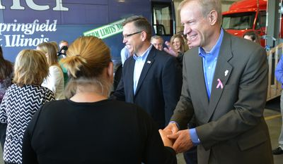 Bruce Rauner, right, the Republican candidate for Illinois governor, greets supporters at a campaign stop at Tennant Trucking, Tuesday, Oct. 21, 2014, in Colona, Ill. (AP Photo/The Dispatch, Todd Mizener)  QUAD CITY TIMES OUT