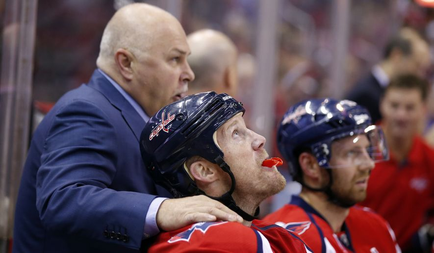 Washington Capitals head coach Barry Trotz puts his hand on Washington Capitals left wing Jason Chimera (25) on the bench in the third period of an NHL hockey game against the Florida Panthers, Saturday, Oct. 18, 2014, in Washington. The Capitals won 2-1, in a shootout. (AP Photo/Alex Brandon)