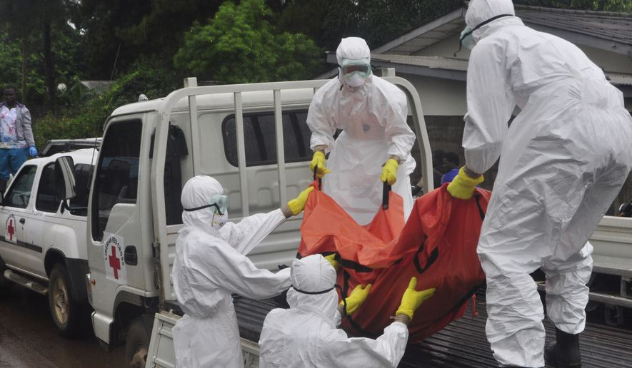 "Health workers  load a body of a man at a back of a truck suspected to have died of Ebola virus in Paynesville Community situated on the outskirts of Monrovia, Liberia, Tuesday, Oct. 21, 2014. Liberian President Ellen Johnson Sirleaf said Ebola has killed more than 2,000 people in her country and has brought it to ""a standstill,"" noting that Liberia and two other badly hit countries were already weakened by years of war. (AP Photo/Abbas Dulleh)"