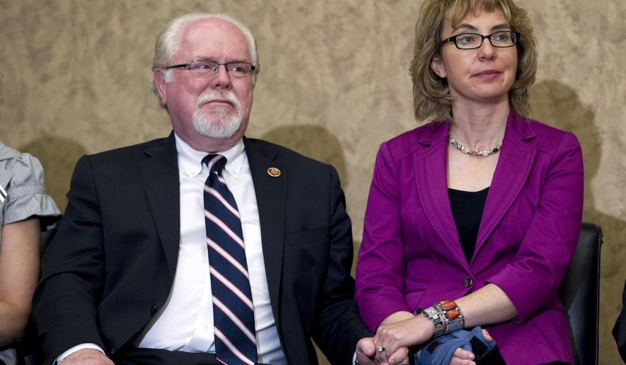 FILE - In this April 16, 2013, file photo, file photo, former Rep. Gabrielle Giffords, D-Ariz., and Rep. Ron Barber, left, D- Ariz., hold hands during the dedication of a room in the Capitol Visitors Center to slain congressional staffer Gabriel Zimmerman in Washington. As the race between Barber, who also was wounded in the 2011 shooting, and Republican Martha McSally has grown tighter in the final weeks before the Nov. 4, 2014, elections, Giffords is playing more of a role by appearing in ads and raising money for her former aide and increasingly turning the race into a debate about guns. (AP Photo/Jose Luis Magana, File)