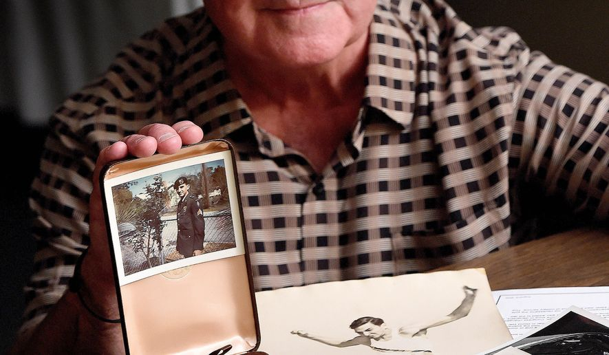 ADVANCE FOR WEEKEND EDITIONS, OCT 25-26 - In this photo taken on Oct. 2, 2014, Don Gassman poses for a photo in Fort Walton Beach, Fla., with a photo of his brother Fred Gassman, who went missing in action during the Vietnam War. (AP Photo/Northwest Florida Daily News, Nick Tomecek)