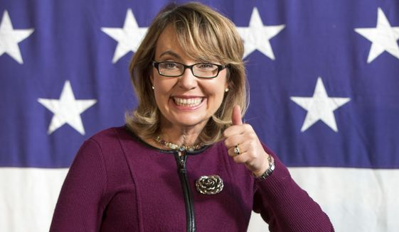 FILE - This Oct. 27, 2013, file photo, shows former U.S. Rep. Gabby Giffords (D-Ariz.), at a fundraiser for U.S. Senate candidate Bruce Braley at the Iowa State Fairgrounds in Des Moines, Iowa. As the race between Rep. Ron Barber D- Ariz., who also was wounded in the 2011 shooting, and Republican Martha McSally has grown tighter in the final weeks before the Nov. 4, 2014, elections, Giffords is playing more of a role by appearing in ads and raising money for her former aide and increasingly turning the race into a debate about guns. (AP Photo/Scott Morgan, File)