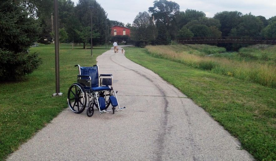 "In this Aug. 20, 2014 photo, an abandoned Mayo Clinic wheelchair sits at rest on the Cascade Creek walking trail near Kutzky Park in Rochester, Minn. In Minnesota's ""Med City,"" wheelchairs are commonplace, and they sometimes end up abandoned in unusual places, such as parking ramps and downtown sidewalks. (AP Photo/Minnesota Public Radio, Elizabeth Baier)"