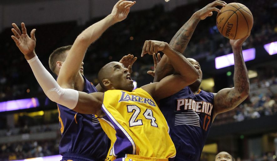 Phoenix Suns' P.J. Tucker, right, gets a rebound against Los Angeles Lakers' Kobe Bryant during the second half of a preseason NBA basketball game Tuesday, Oct. 21, 2014, in Anaheim, Calif. The Suns won 114-108 in overtime. (AP Photo/Jae C. Hong)