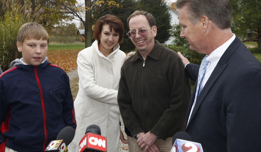 Jeffrey Fowle, center, smiles as he stands with his family and with attorney, Timothy Tepe, far right, at his home in West Carrollton, Ohio, Wednesday, Oct. 22, 2014. Mr. Fowle was arrested and held for nearly six months in North Korea after leaving a Bible at a nightclub. Christian evangelism is considered a crime in North Korea.   (AP Photo/David Kohl)