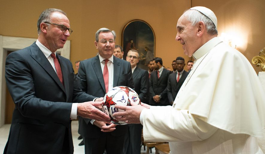 In this photo provided by the Vatican newspaper L'Osservatore Romano,  Pope Francis receives an autographed soccer ball by Bayern Munich's CEO Karl-Heinz Rummenigge, left, and Bayern Munich's President Karl Hopfner, center, during a private audience with team and officials at the Vatican, Wednesday, Oct. 22, 2014. (AP Photo/L'Osservatore Romano)