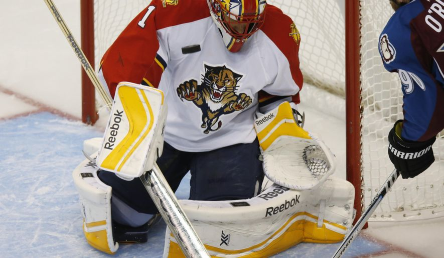 Florida Panthers goalie Roberto Luongo, left, makes stop of shot off the stick of Colorado Avalanche center Ryan O'Reilly in the second period of an NHL hockey game in Denver on Tuesday, Oct. 21, 2014. (AP Photo/David Zalubowski)