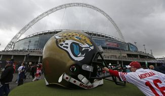 A 49ers supporter reaches out to touch a giant Jaguars helmet as fans arrive at Wembley Stadium in London to watch the NFL football game between San Francisco 49ers and Jacksonville Jaguars, Sunday, Oct. 27, 2013. (AP Photo/Sang Tan)