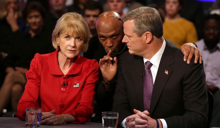 Massachusetts gubernatorial candidates Democrat Martha Coakley, left, and Republican Charlie Baker, right, listen to a technician moments before a televised debate at WGBH television studios, Tuesday, Oct. 21, 2014, in Boston. Baker and Coakley are locked in a dead heat and each are hoping to lure in more supporters while avoiding any gaffe that could cost them the election. (AP Photo/The Boston Globe, Barry Chin, Pool)