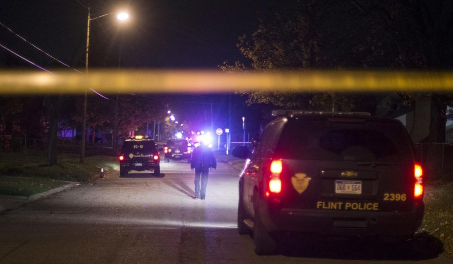 In this photo taken on Tuesday night, Oct. 21, 2014, Flint Police investigate the scene outside a home where a was shot and killed in in Flint, Mich. Police say one man is dead and another wounded following separate shootings less than 20 minutes apart in Flint. (AP Photo/The Flint Journal,  Erin Kirkland) LOCAL TELEVISION OUT; LOCAL INTERNET OUT