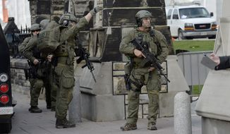 A Royal Canadian Mounted Police intervention team walks past a gate on Parliament hill in Ottawa Wednesday Oct. 22, 2014. A soldier standing guard at the National War Memorial has been shot by an unknown gunman and there have been reports of gunfire inside the halls of Parliament. Emergency responders are still on the scene as paramedics performed CPR on the soldier before he was taken away by ambulance.  (AP Photo/The Canadian Press, Adrian Wyld)