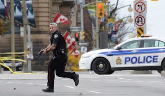 An Ottawa police officer runs with his weapon drawn outside Parliament Hill in Ottawa on Wednesday Oct. 22, 2014.  A soldier standing guard at the National War Memorial was shot by an unknown gunman and people reported hearing gunfire inside the halls of Parliament. Prime Minister Stephen Harper was rushed away from Parliament Hill to an undisclosed location, according to officials. (AP Photo/The Canadian Press, Sean Kilpatrick)