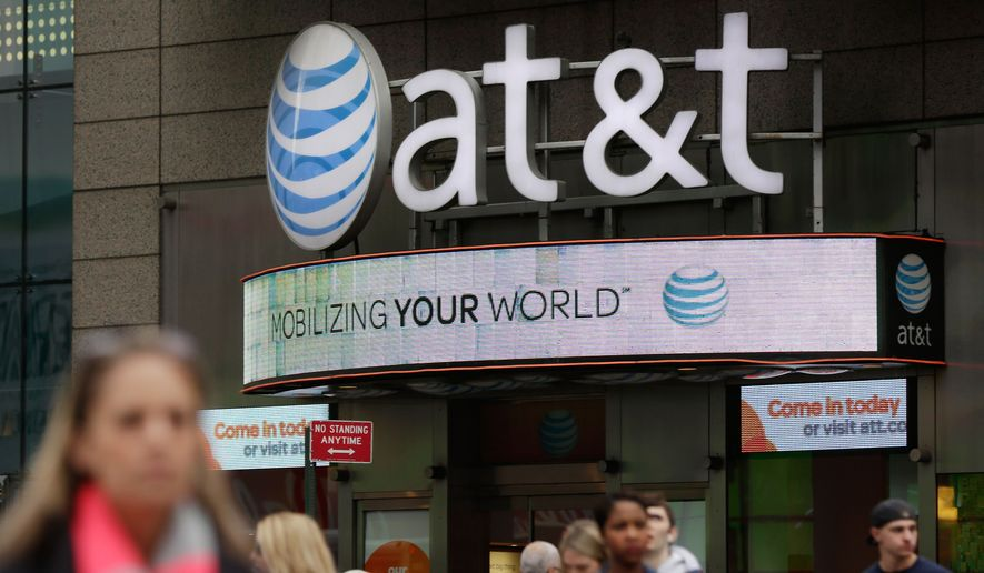 In this Tuesday, Oct. 21, 2014 photo, people pass an AT&T store, in New York's Times Square. (AP Photo/Richard Drew)
