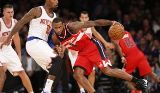 Washington Wizards forward Rasual Butler, right, drives into New York Knicks guard J.R. Smith, front left,in the first half of an NBA basketball game at Madison Square Garden in New York, Wednesday, Oct. 22, 2014. The Knicks defeated the Wizards 103-100. (AP Photo/Kathy Willens)