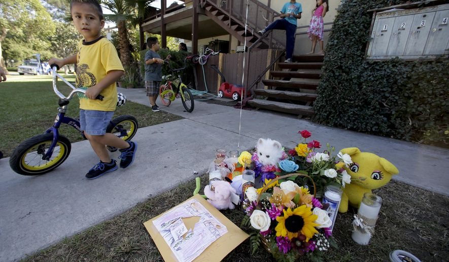 Neighborhood children walk by a makeshift memorial on Thursday, Oct. 23, 2014, in  Anaheim, Calif., near where Ximena Meza, 9, was shot while playing with her two sisters and other children Wednesday evening,  A $5,000 reward is being offered to help capture the killer. (AP Photo/Chris Carlson)
