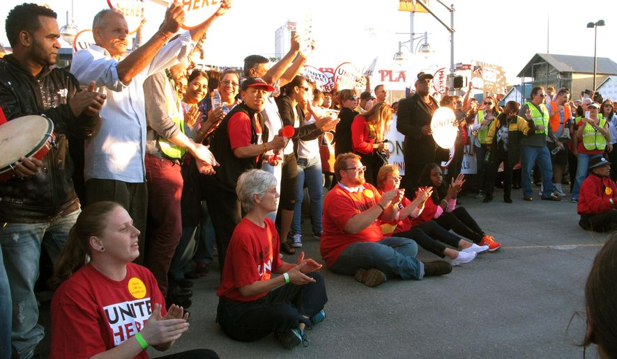 In this Oct. 8, 2014 photo, casino workers union members sit down on the Atlantic City Expressway in Atlantic City N.J. and block traffiic to protest givebacks demanded and later won by the Trump Taj Mahal casino in its efforts to avoid closing down. On Oct. 22, 2014, the company backed off its threat to close the Taj Mahal on Nov. 13, saying it still may close by the end of the year, but will remain open throughout the month of November.  (AP Photo/Wayne Parry)