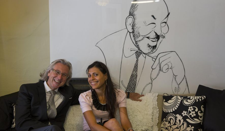 ADVANCED FOR MONDAY OCT. 27 AND THEREAFTER Vice President of Store Development, Ignaz Gorischek, left, and Visual Manager, Mari Lavergne, right, pose in front of an Al Hirschfeld caricature of Stanley Marcus at the Neiman-Marcus flagship store in Dallas, Texas on July 30, 2014. (AP Photo/The Dallas Morning News, Brittany Sowacke) MANDATORY CREDIT; MAGS OUT; TV OUT; INTERNET USE BY AP MEMBERS ONLY; NO SALES
