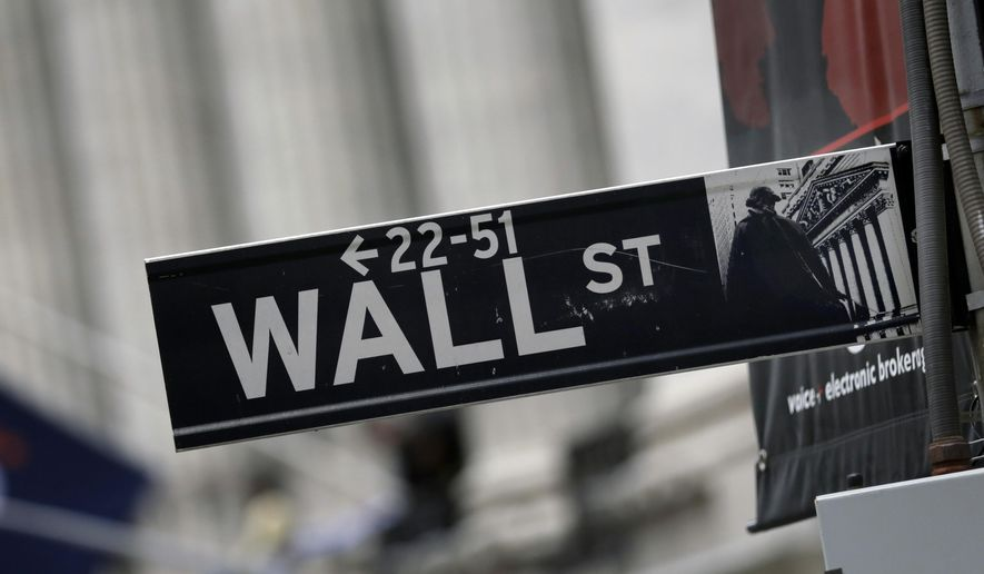 This Oct. 2, 2014 photo shows a Wall Street sign adjacent to the New York Stock Exchange, in New York. Earnings gains from General Motors, 3M and other big companies are driving stocks sharply higher in early trading Thursday, Oct. 23, 2014. (AP Photo/Richard Drew)