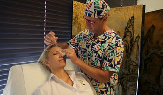 In this Tuesday, Oct. 14, 2014 photo, Italian plastic surgeon Roberto Viel gives Italian Irina Tzoneva, a 41-year-old restaurant manager, a treatment at London Centre for Aesthetic Surgery in Dubai, United Arab Emirates. Dubai, the emirate known for its celebration of over-the-top glamour and luxury, is racing ahead to dominate the Middle East's plastic surgery market with plans to attract half a million medical tourists in six years. (AP Photo/Kamran Jebreili)