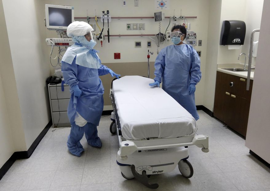 FILE - In this Oct. 8, 2014, file photo, Bellevue Hospital nurse Belkys Fortune, left, and Teressa Celia, Associate Director of Infection Prevention and Control, pose in protective suits in an isolation room, in the Emergency Room of the hospital, during a demonstration of procedures for possible Ebola patients in New York. A doctor who recently returned to New York City from West Africa is being tested for the Ebola virus. The doctor had a fever and gastrointestinal symptoms and was taken Thursday to Manhattan's Bellevue Hospital. (AP Photo/Richard Drew, File)