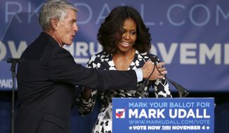 First lady Michelle Obama, right, is thanked by Sen. Mark Udall, D-Colo., after rally for his re-election campaign in Denver on Thursday, Oct. 23, 2014. Obama will make another stop on Thursday when she appears at a rally for Udall's campaign in Moby Arena on the campus of Colorado State University in Fort Collins, Colo. (AP Photo/David Zalubowski)