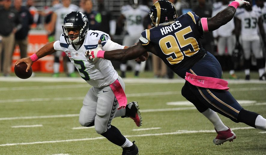 Seattle Seahawks quarterback Russell Wilson, left, scrambles away from St. Louis Rams defensive end William Hayes during the first half of an NFL football game Sunday, Oct. 19, 2014, in St. Louis. (AP Photo/L.G. Patterson)
