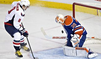 Washington Capitals' Alex Ovechkin (8) is stopped by Edmonton Oilers goalie Ben Scrivens (30) during the third period of an NHL hockey game in Edmonton, Alberta, on Wednesday, Oct. 22, 2014. The Oilers won 3-2. (AP Photo/The Canadian Press, Jason Franson)