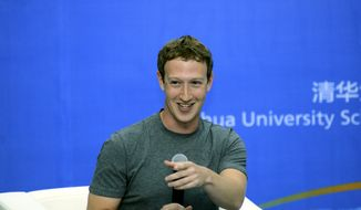 In this Oct. 22, 2014, photo released by Tsinghua University, Facebook co-founder Mark Zuckerberg speaks during a dialogue with students as a newly appointed member to the advisory board for Tsinghua University School of Economics and Management in Beijing, China. China may ban Facebook, but not its co-founder Zuckerberg, and he entertained an audience of students with a 30-minute chat in his recently learned Mandarin Chinese at the prestigious Beijing university. (AP Photo/Tsinghua University)