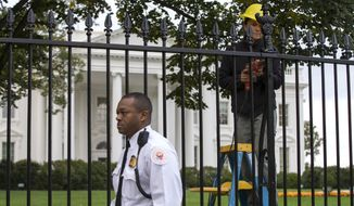 A Secret Service police officer walks outside the White House in Washington, Thursday, Oct. 23, 2014, as a maintenance worker performs fence repairs as part of a previous fence restoration project. Dominic Adesanya, the 23-year-old Maryland man who climbed over the White House fence, was ordered held without bond in an appearance Thursday before a federal magistrate judge. He has been charged with unlawfully entering the restricted grounds of the White House and harming two police dogs. (AP Photo/Evan Vucci)