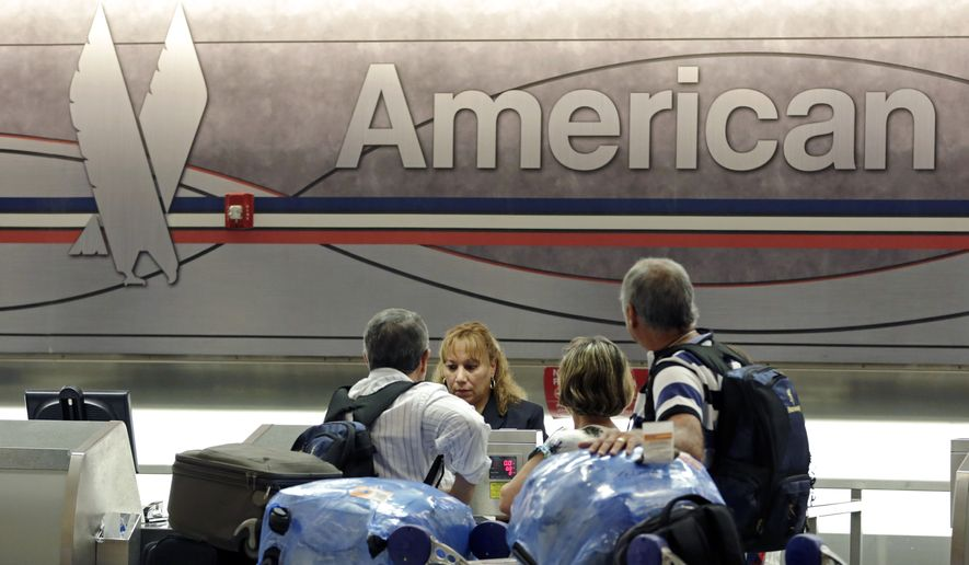In this photo taken Tuesday, May 27, 2014, passengers check in at the American Airlines counter at Miami International Airport in Miami. American Airlines reports quarterly financial results on Thursday, Oct. 23, 2014. (AP Photo/Alan Diaz)