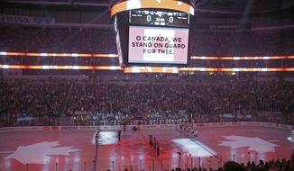As a tribute to the victims of the Ottawa shootings, the national anthem of Canada is sung before an NHL hockey game between the Pittsburgh Penguins and the Philadelphia Flyers in Pittsburgh, Wednesday, Oct. 22, 2014. (AP Photo/Gene J. Puskar)