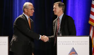 Colorado Gov. John Hickenlooper, right, shakes hands with his opponent, Republican candidate for governor Bob Beauprez, at the start of a debate in Denver, Thursday, Oct. 23, 2014. (AP Photo/Brennan Linsley)
