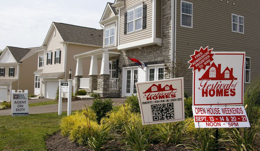 FILE - In this file photo made on Wednesday, Sept. 10, 2014, signs welcome visitors to a model home as construction is under way at a housing development in Zelienople, Pa. Freddie Mac reports on average U.S. mortgage rates for this week on Thursday, Oct. 23, 2014. (AP Photo/Keith Srakocic, File)