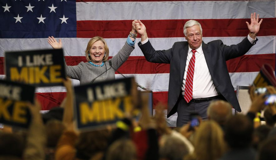 Hillary Rodham Clinton and Democratic gubernatorial candidate Sen. Mike Michaud acknowledge applause during a rally for Michaud, Friday, Oct. 24, 2014, at Scarborough High School in Scarborough, Maine. (AP Photo/Robert F. Bukaty)
