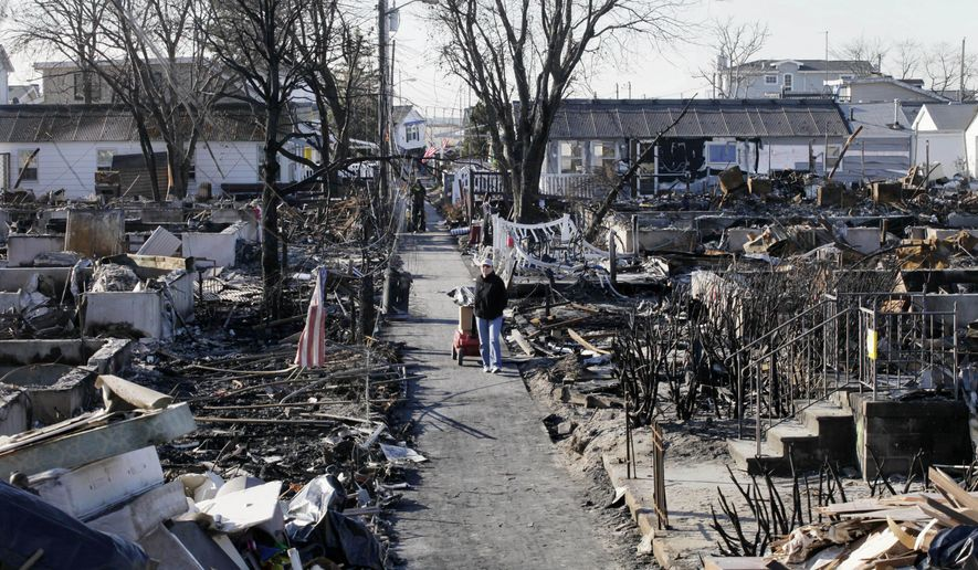 ADVANCE FOR USE SUNDAY, OCT. 26, 2014, AND THEREAFTER- FILE- This Nov. 14, 2012, file photo shows Louise McCarthy carting belongings from her flood-damaged home as she passes the charred ruins of other homes in the Breezy Point section of the Queens borough of New York. A fire leveled 130 houses in the beachfront community during Superstorm Sandy. (AP Photo/Mark Lennihan, File)