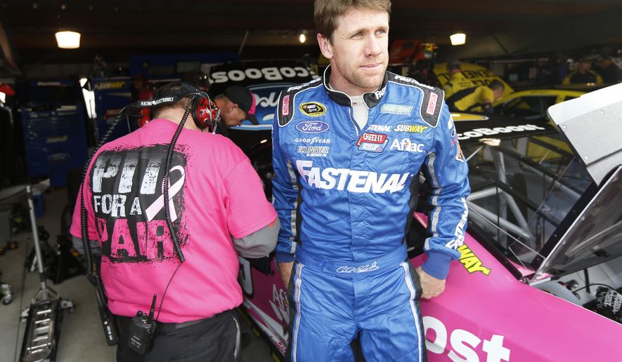 Carl Edwards leaves the garage after practice for Sunday's Sprint Cup Series NASCAR auto race at Martinsville Speedway in Martinsville, Va., Friday, Oct. 24, 2014. (AP Photo/Steve Helber)