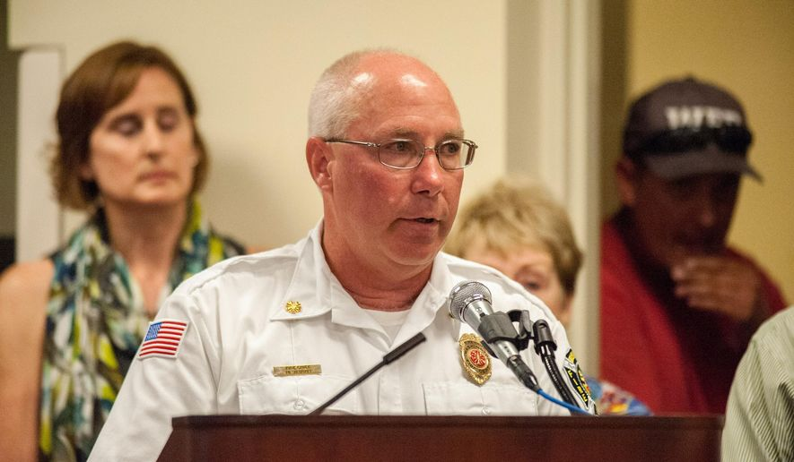 In this Monday, July 7, 2014 photo, Washington Fire Chief Mike Vaughn spoke briefly during the Washington City Counsel meeting as residents came to support him at the Washington District Library in Washington, Ill.  The Washington fire chief who won state and national awards for his response to a 2013 tornado has announced his resignation. (AP Photo/Journal Star, Ting Shen)