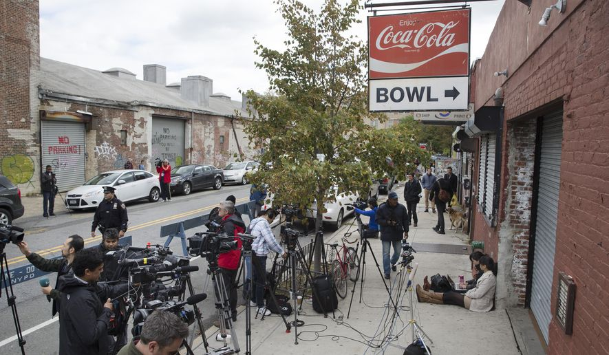 Journalists setup outside The Gutter bowling alley as it remains closed after it was visited by Craig Spencer, a Doctors Without Borders physician who tested positive for the Ebola virus, Friday, Oct. 24, 2014, in the Williamsburg neighborhood of the Brooklyn borough of New York. (AP Photo/John Minchillo)