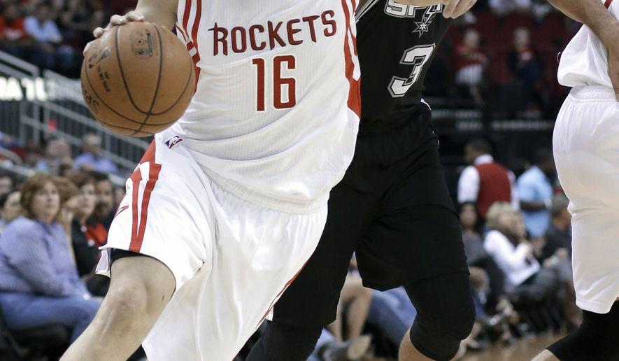 San Antonio Spurs' Marco Belinelli (3) grabs for Houston Rockets' Kostas Papanikolaou (16) during the first half of an NBA preseason basketball game Friday, Oct. 24, 2014, in Houston. (AP Photo/Pat Sullivan)