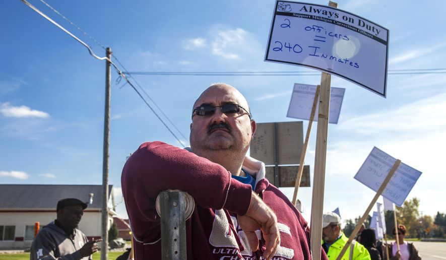 St. Louis Corrections Officer Scott Bragiel, holds up his protest sign about the recent cuts of correction officers near the Saginaw Correctional Facility, 9625 Pierce in Freeland, Thursday, Oct. 23, 2014. Saginaw Corrections Officer Kevin Ott was recently attacked by a prisoner and sent to the hospital Friday, Oct. 17. He was one of two correction officers assigned to a block of 240 prisoners. (AP Photo/The Saginaw News, Neil Barris)