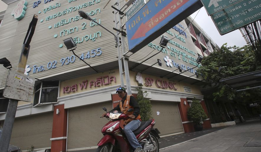 A motorcycle taxi drives past a clinic in Bangkok, Thailand, Friday, Oct. 24, 2014. Authorities say a British woman has died at the clinic under anesthesia during an operation to fix the previous cosmetic surgery she had at the same facility. (AP Photo/Sakchai Lalit)