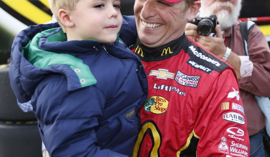 Jamie McMurray celebrates after winning the pole with his son, Carter, after qualifying for Sunday's Sprint Cup Series auto race at Martinsville Speedway in Martinsville, Va., Friday, Oct. 24, 2014. (AP Photo/Steve Helber)