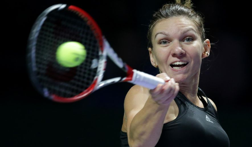 Romania's Simona Halep hits  forehand return to Serbia's Ana Ivanovic during their singles match at the WTA tennis finals in Singapore, Friday, Oct. 24, 2014. (AP Photo/Mark Baker)